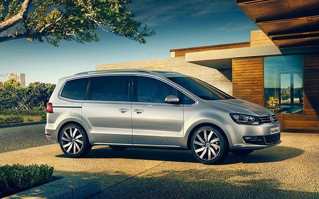 silver Volkswagen Sharan side on outside a modern house