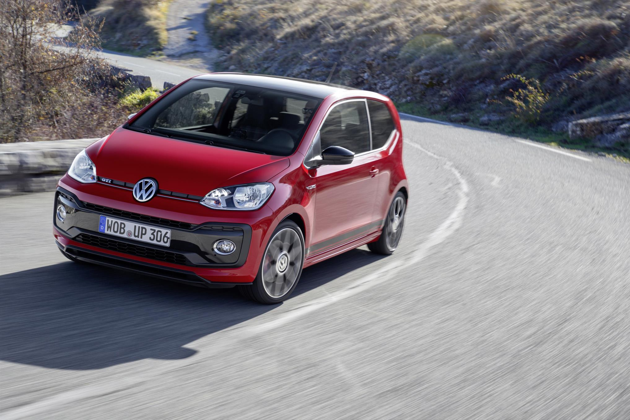 Red VW up GTI city car driving on winding road