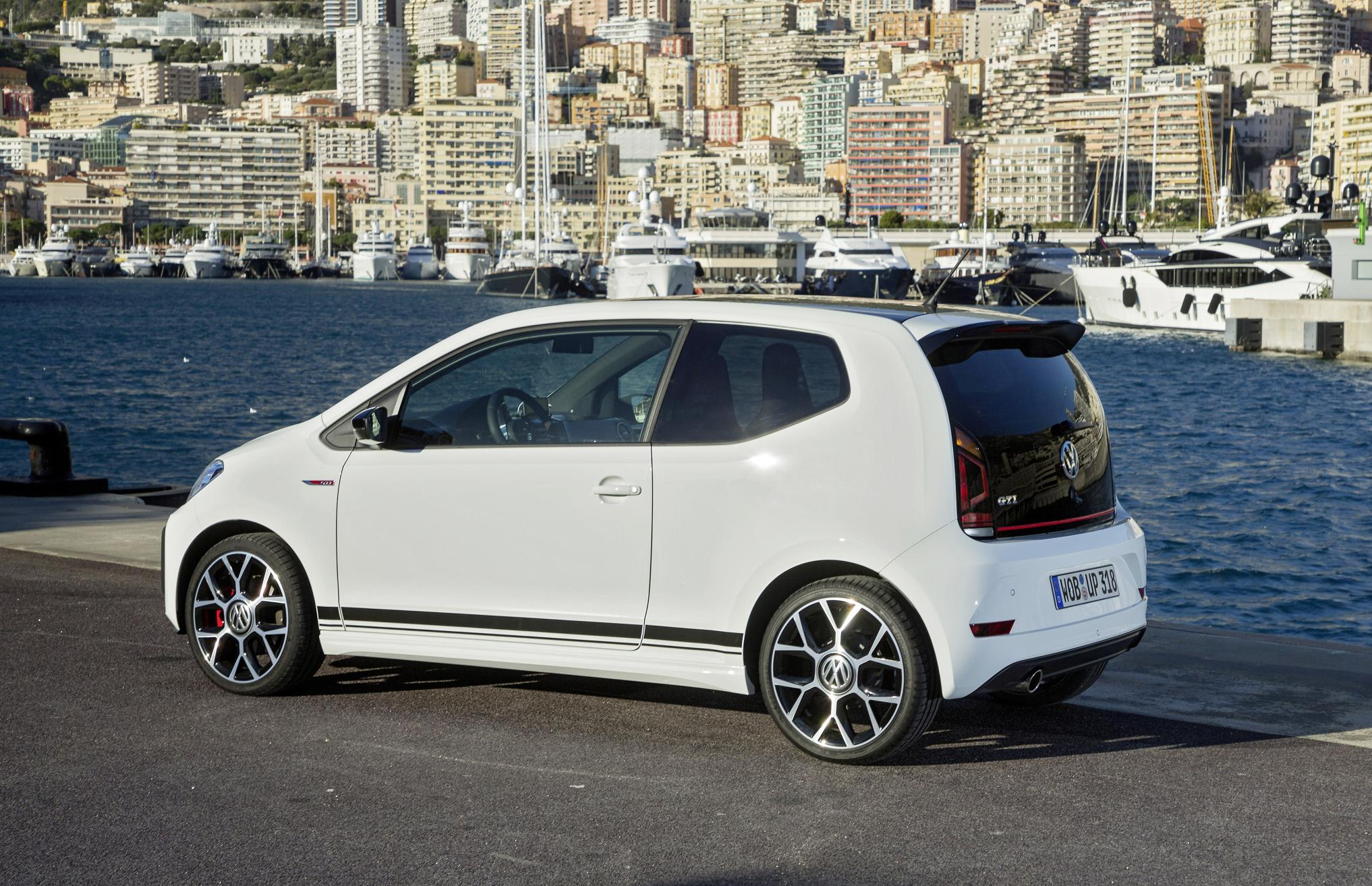 White side of VW up GTI city car parked by the sea near a boat harbour