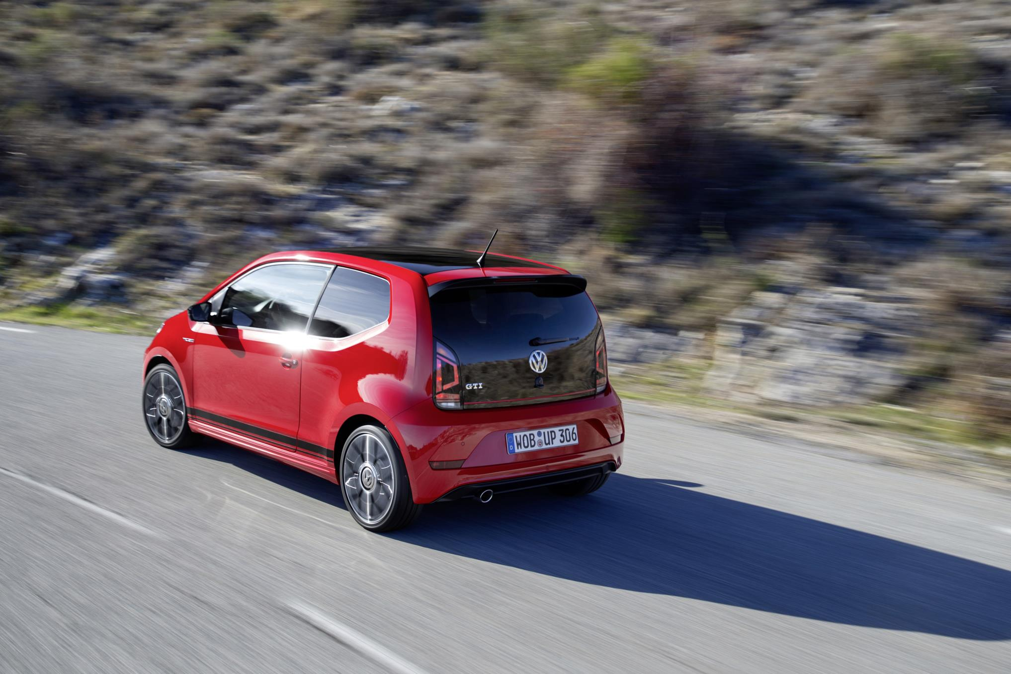 Red Volkswagen up! speeding along on right hand-side of the road