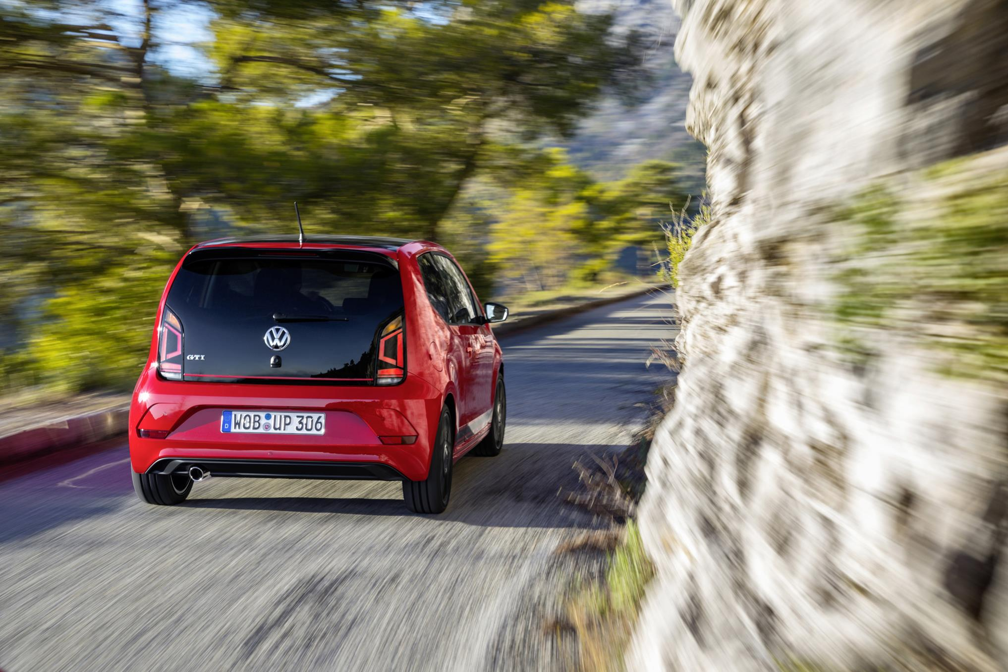 Red Volkswagen up GTI city car driving down country road