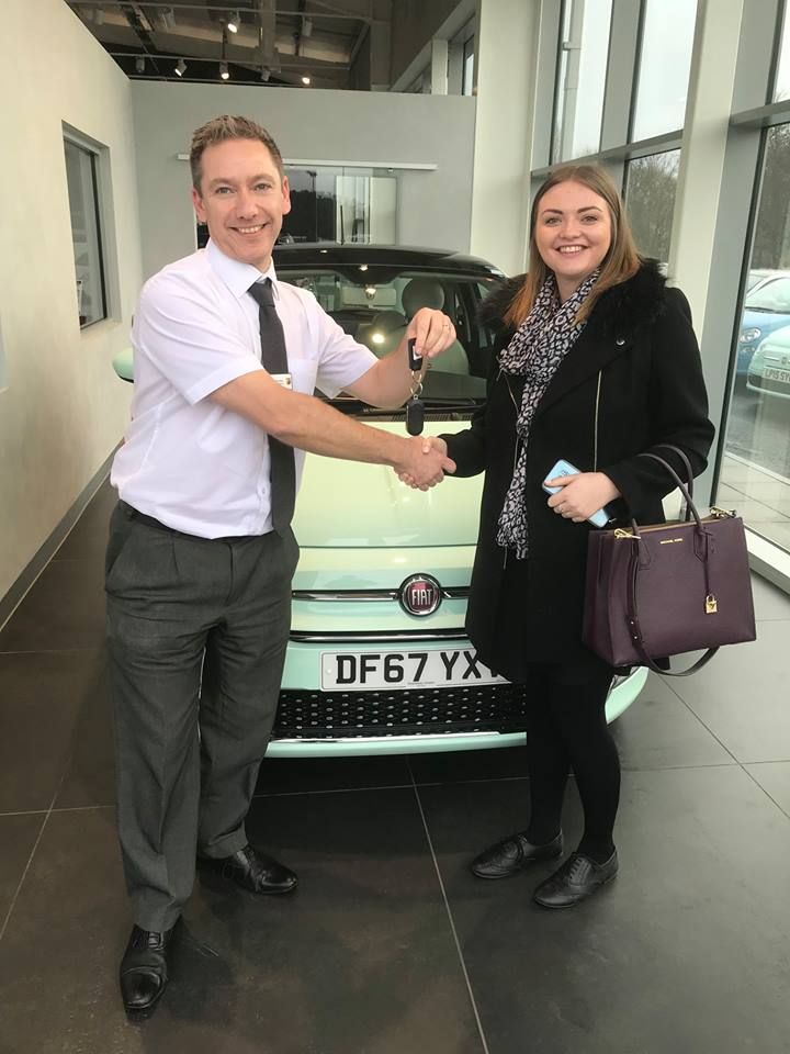 Smiley car Sales Executive hands over the keys of a new FIAT 500 to a very happy owner