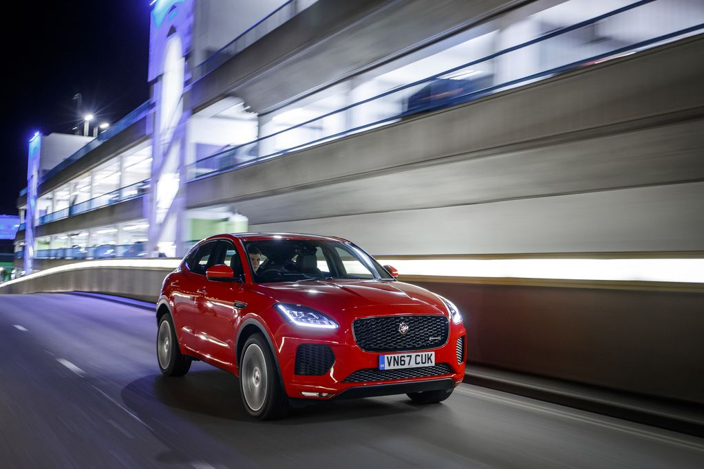 Red Jaguar E-Pace at night-time going past well-lit multi-storey carpark