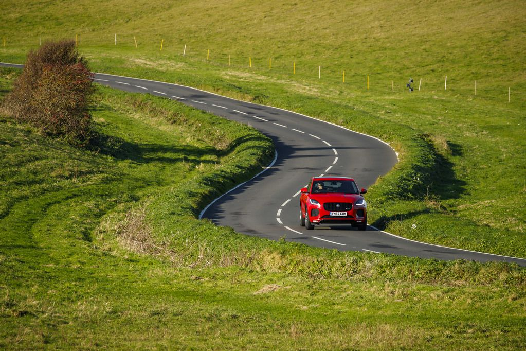 Red Jaguar E-Pace on winding lane between beautiful green fields