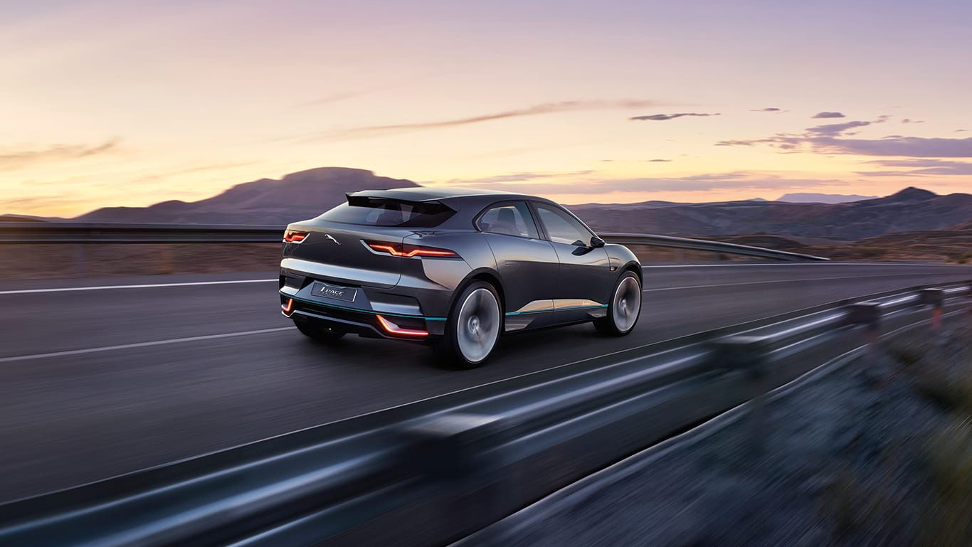 Jaguar I-pace driving at speed at dusk with lights on