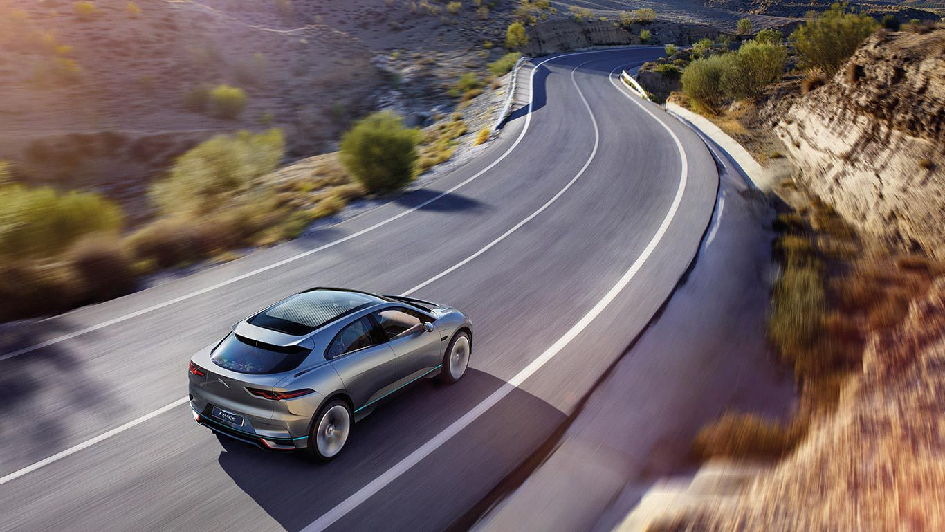 Jaguar I-Pace on winding road photographed from above and behind