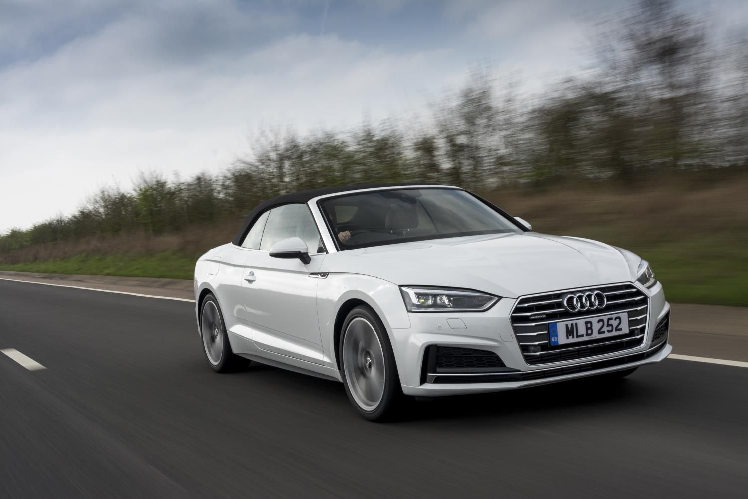 White Audi A5 Cabriolet with the roof down driving towards you on an open road