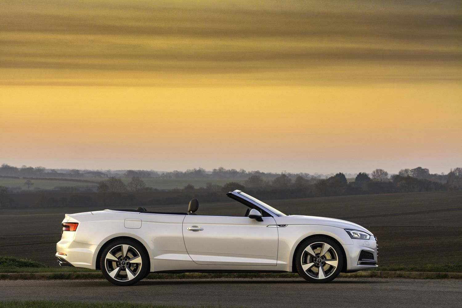 White Audi A5 Cabriolet viewes side on with a beautiful subset behind it.