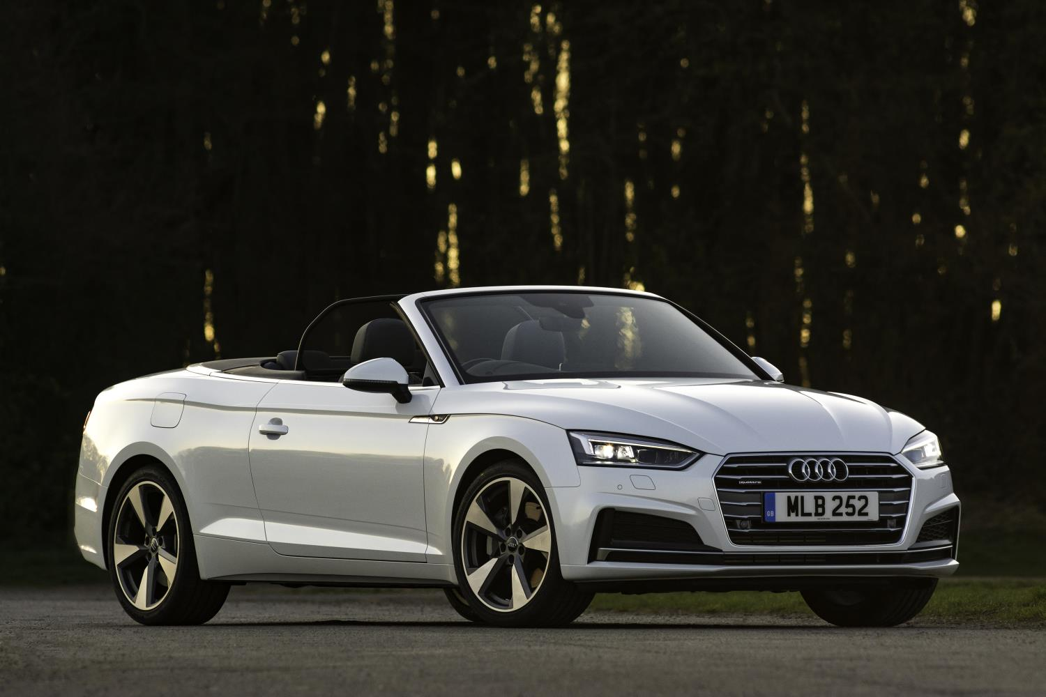 White Audi A5 Cabriolet stationary with the roof down at dusk