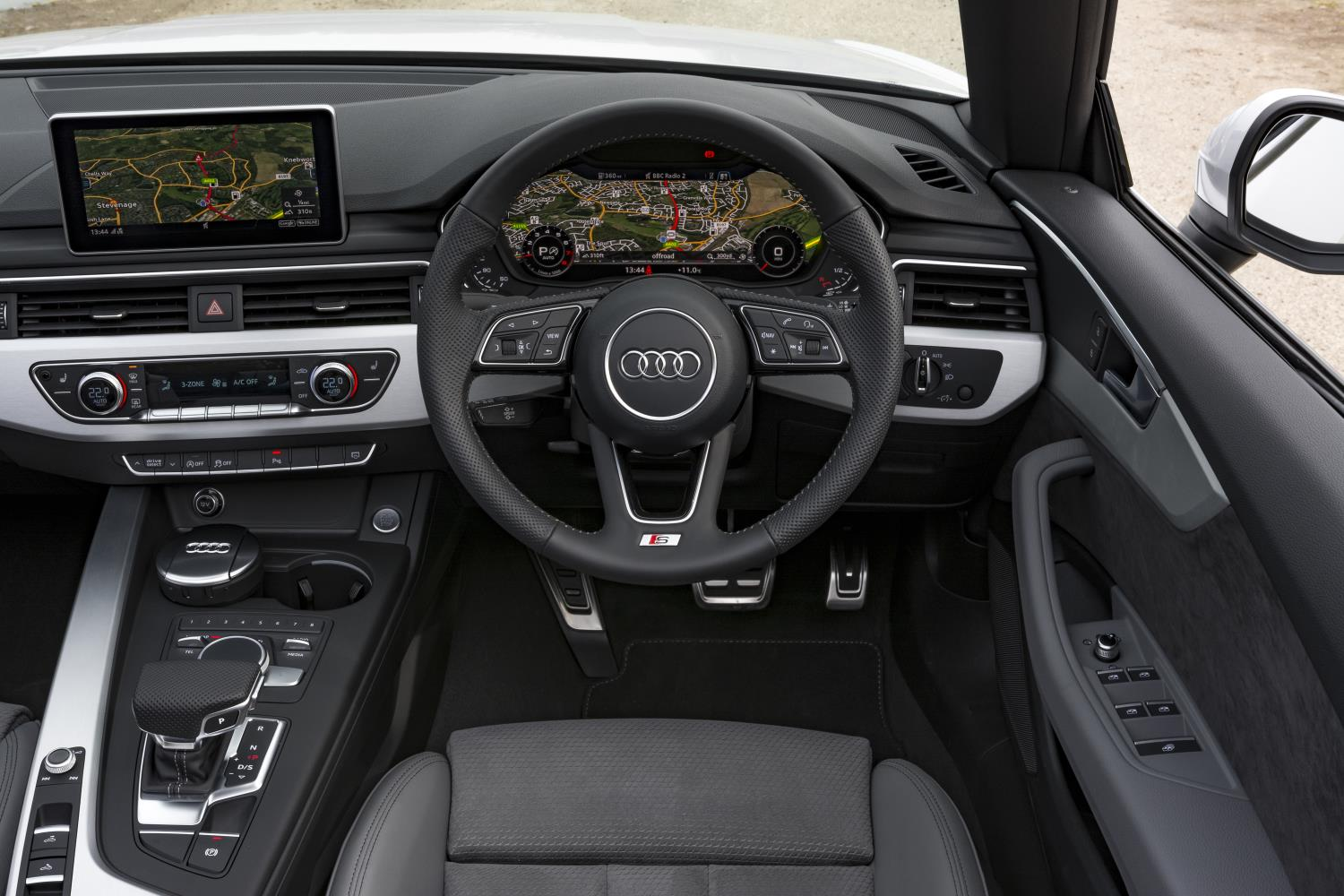 Driver's cockpit in a white Audi A5 Cabriolet with grey leather interior and the roof down