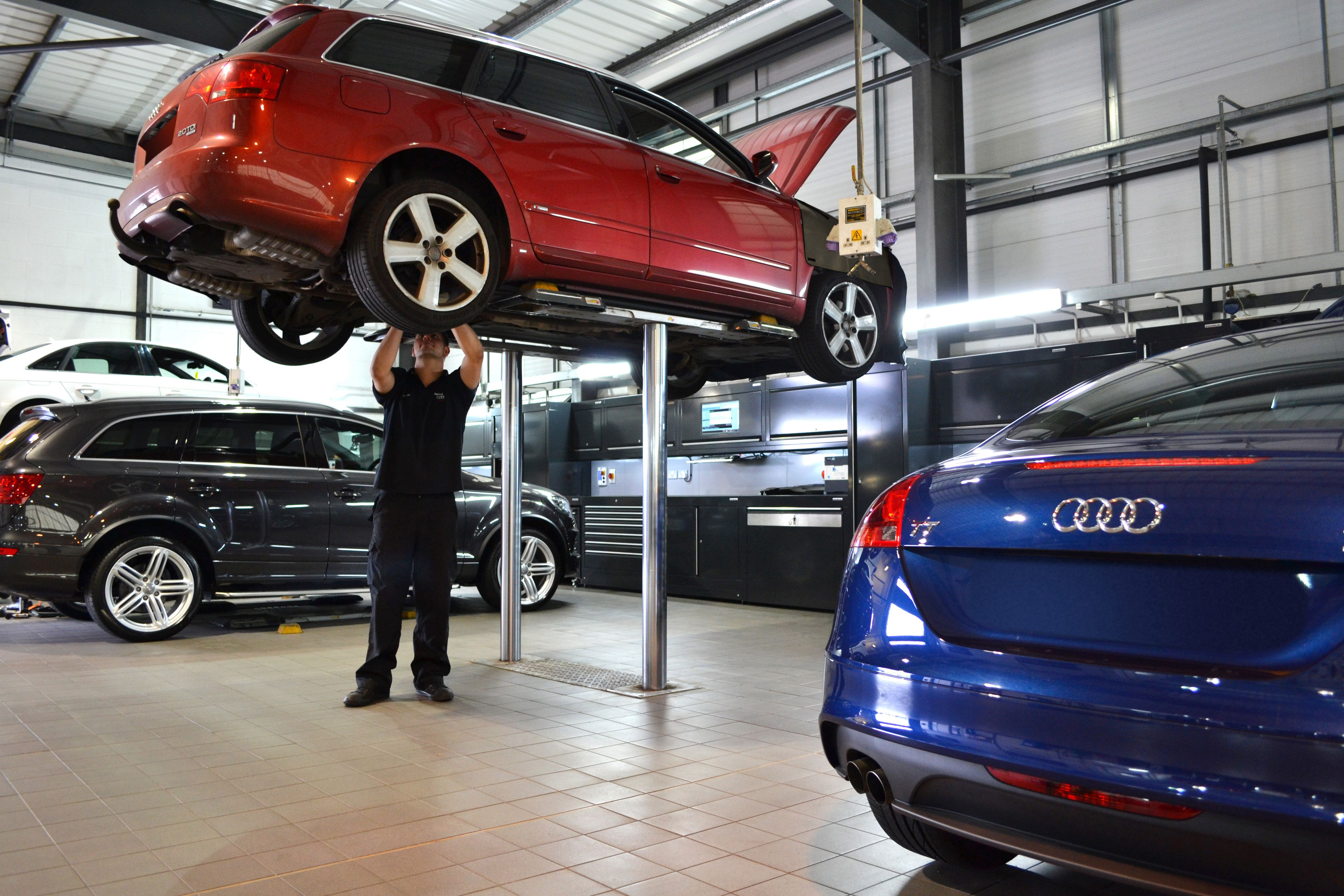 Red metallic Audi on ramp being worked on by Technician