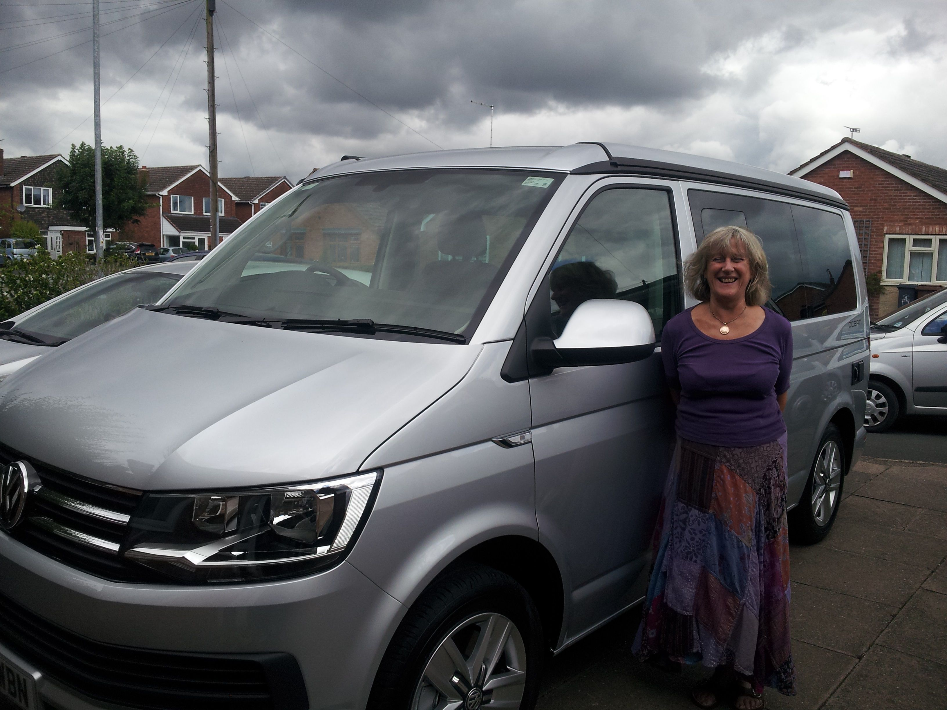 Woman stood beside a Volkswagen California campervan
