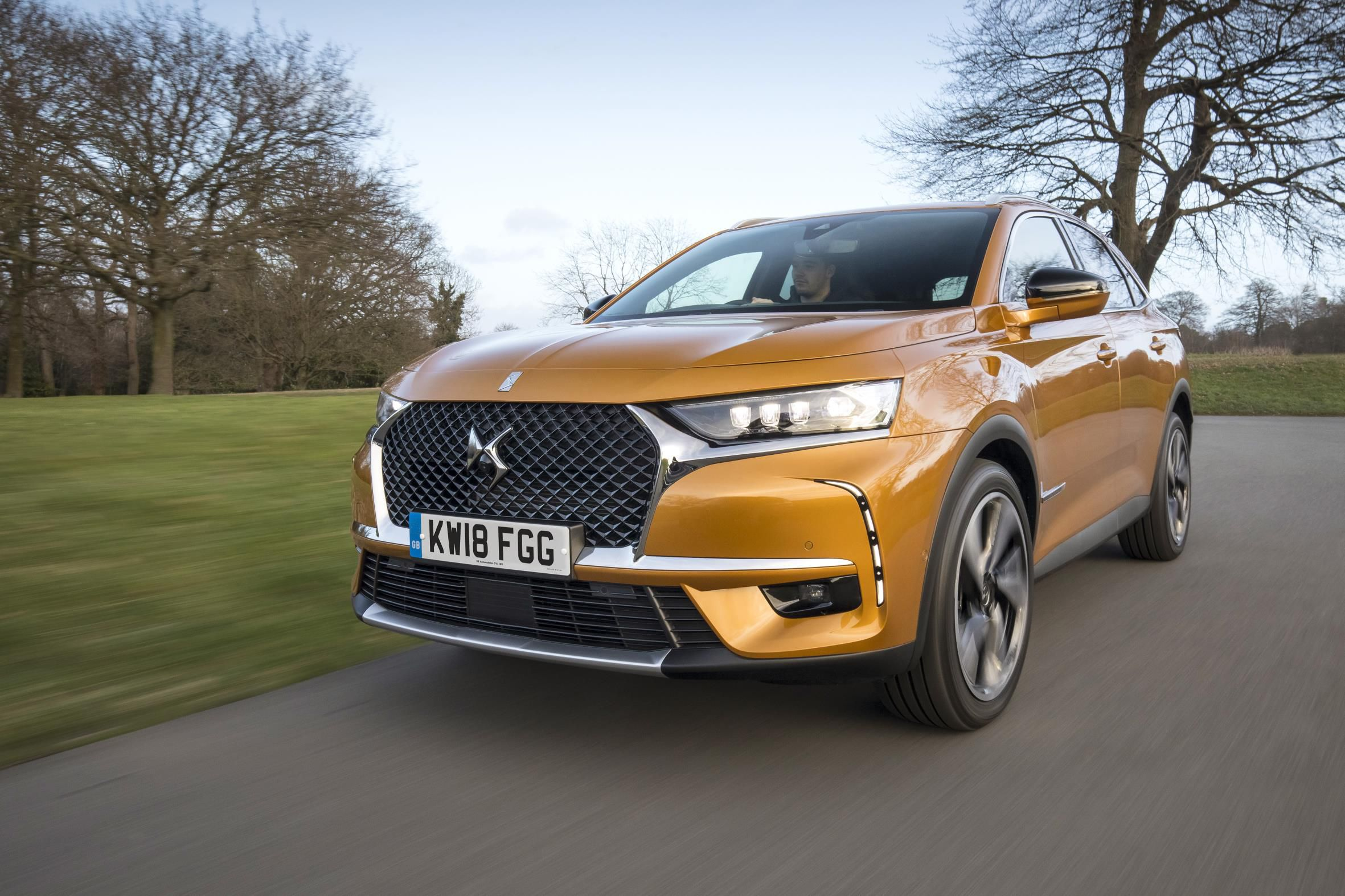 DS7 Crossback in metallic orange driving through the country