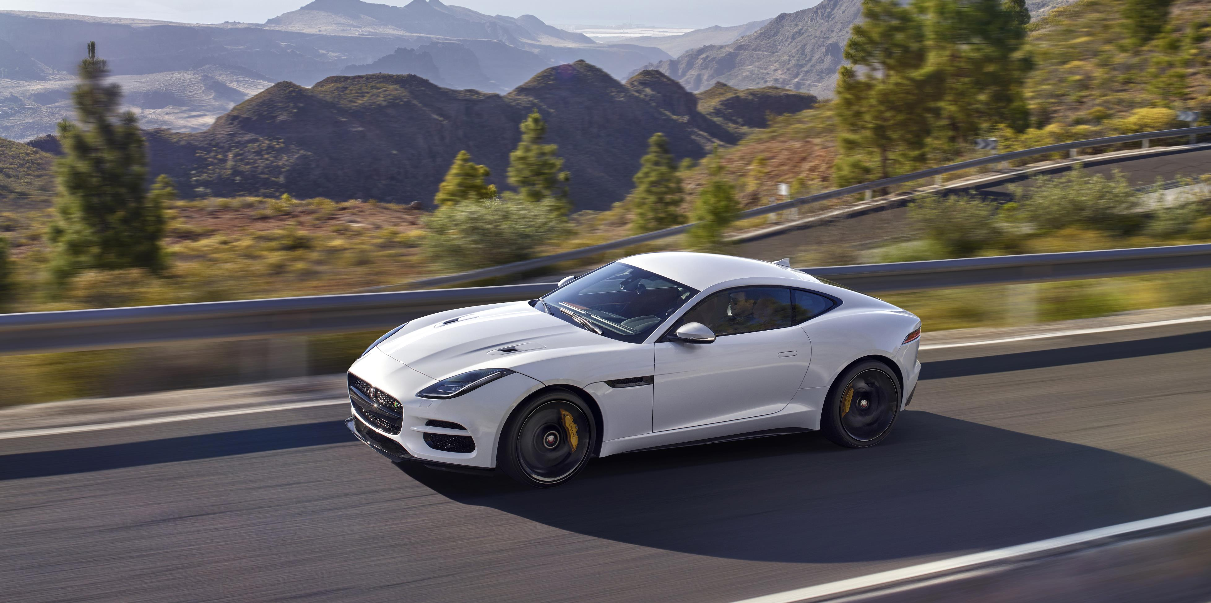 White Jaguar F-Type speeding through stunning countryside