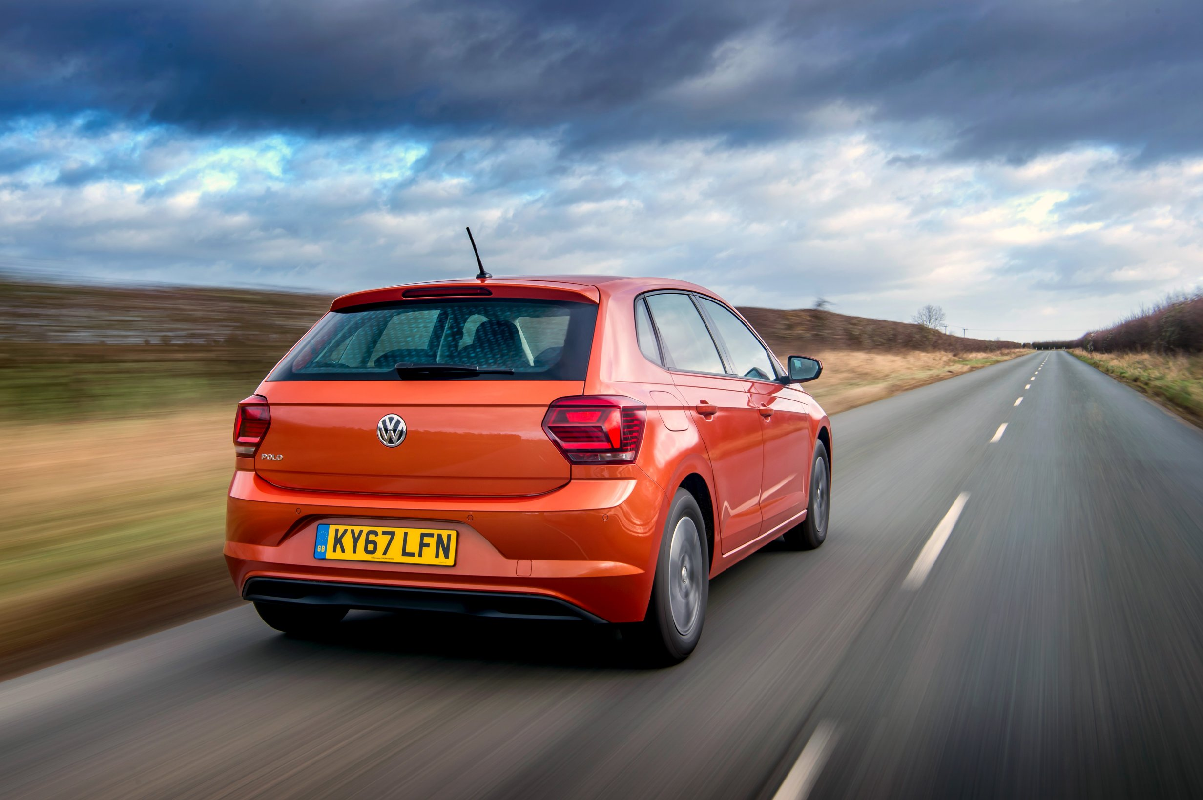 Metallic orange new Volkswagen Polo from behind driving on a lane