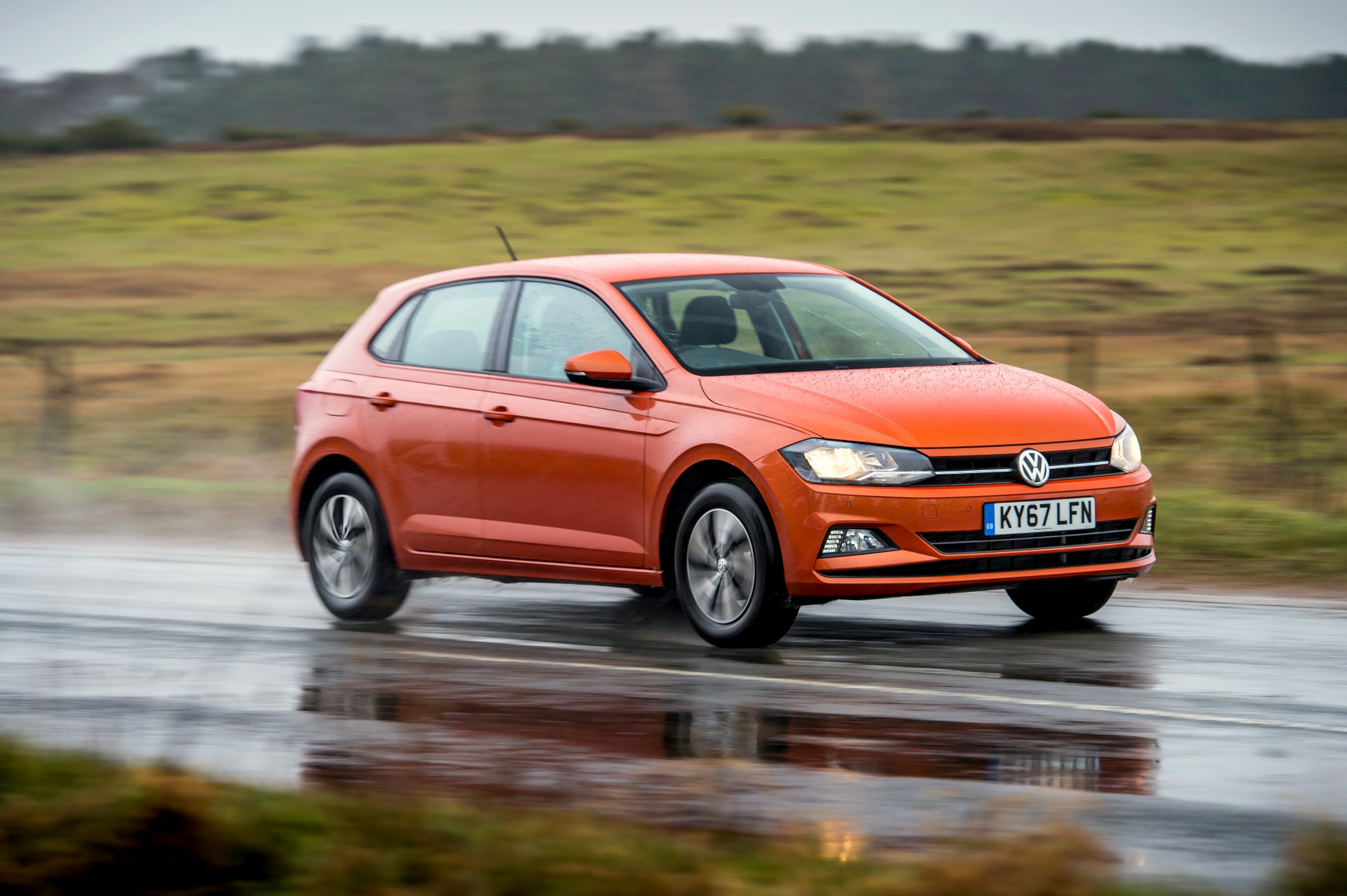 Orange metallic Volkswagen Polo driving on a very wet road