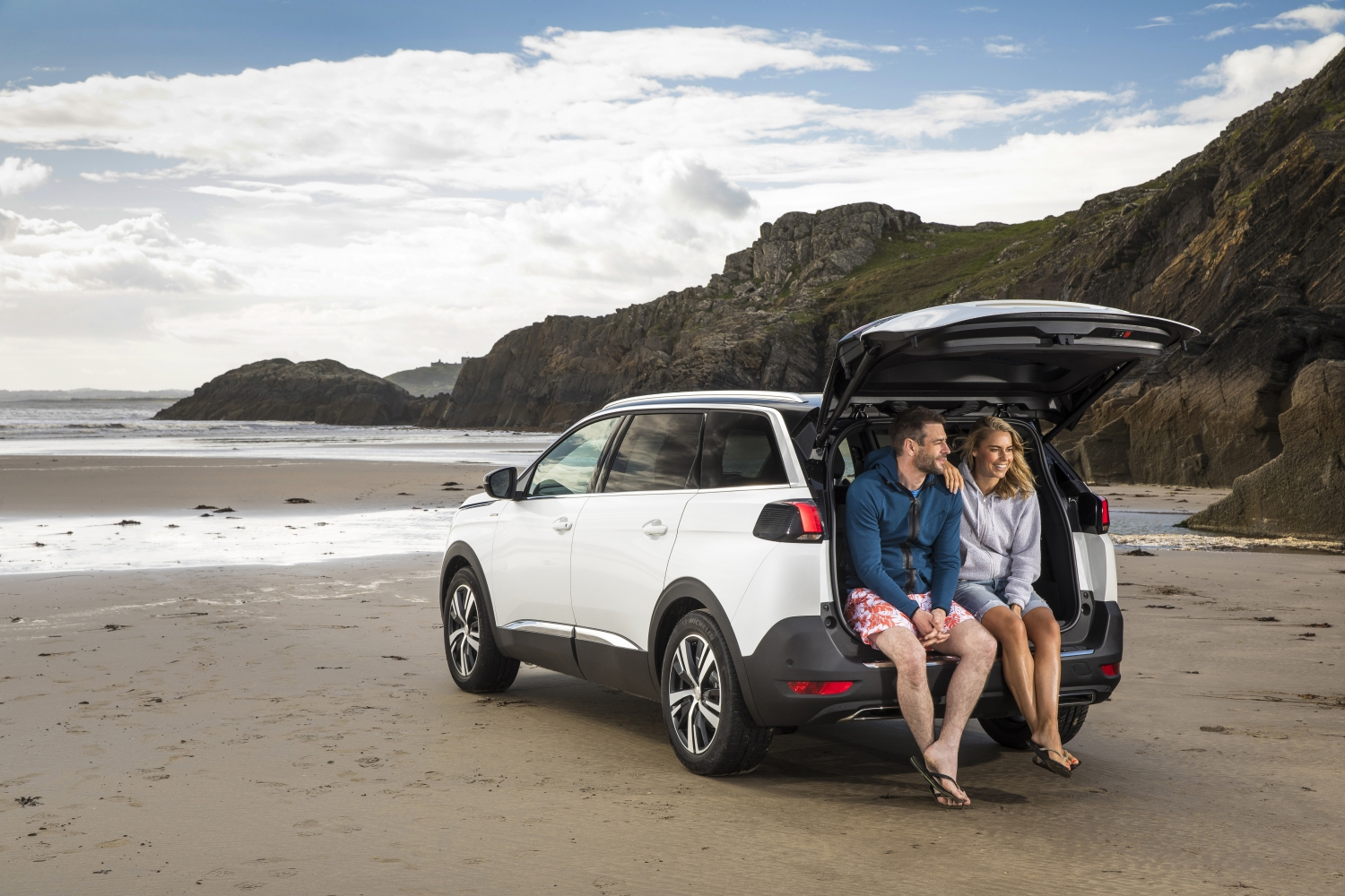 Couple sat on the rear of Peugeot 5008