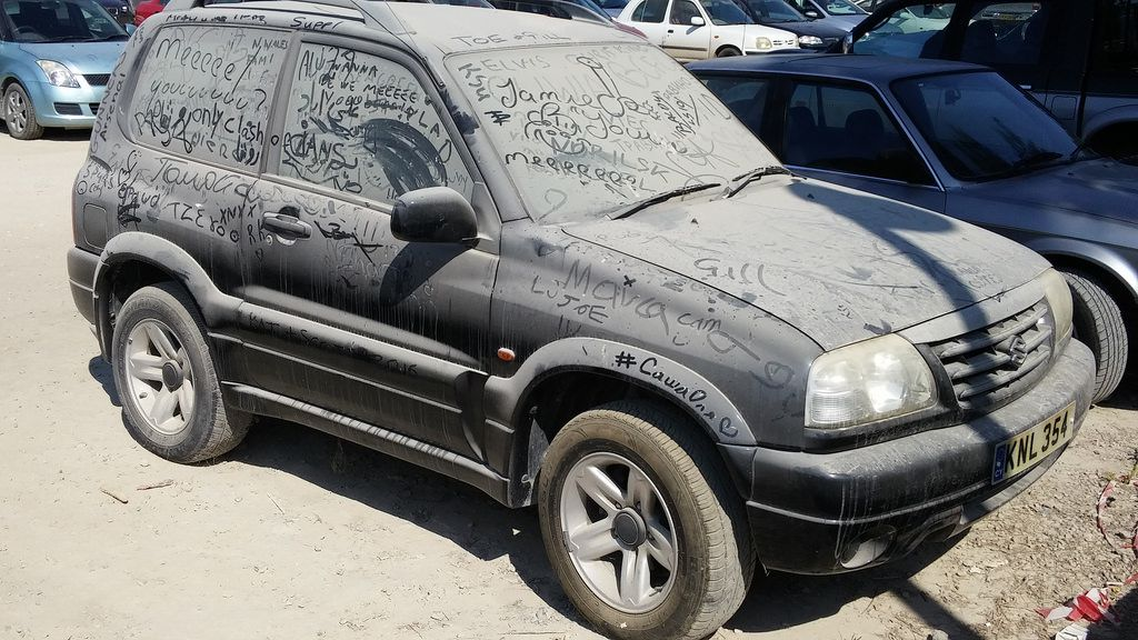 Extremely dirty car with writing in the dirt