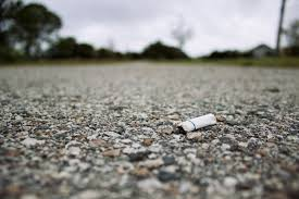Cigarette butt on road after being thrown out of a car