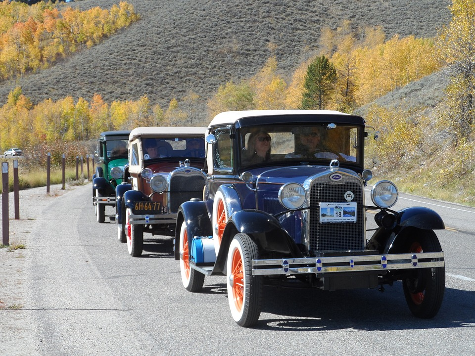 Parade of old Ford motor cars through countryside